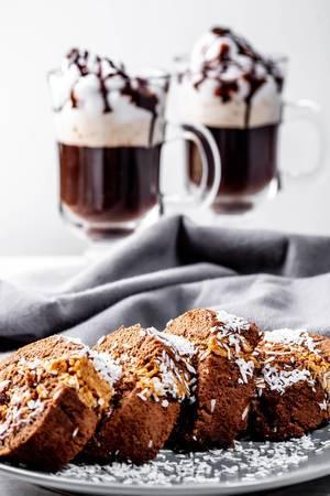 Biskuitrolle als Desert mit zwei Tassen Kaffee im Glas