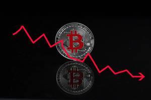 Bitcoin Absturz - Bitcoin Münze mit einer roten Falllinie auf schwarzem Hintergrund