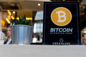 Bitcoin accepted display on a restaurant table next to a little plant