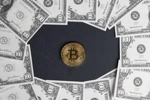 Bitcoin auf schwarzem Hintergrund umringt von 100-Dollar-Noten