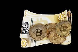 Bitcoin-Banknoten vor schwarzem Hintergrund