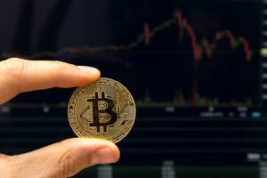 Bitcoin between to fingers in detail infront of falling stock prices on a display