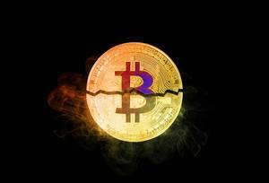Bitcoin broken in half on black background