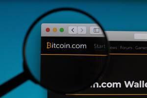 Bitcoin.com Schriftzug und Logo unter einer Lupe
