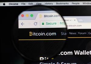 Bitcoin-Logo am PC-Monitor, durch eine Lupe fotografiert
