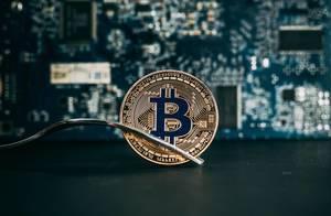Bitcoin Münze zwischen den Zacken einer Gabel