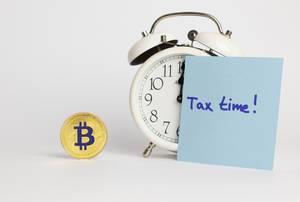 Bitcoin Steuerberechnung - Ein Wecker und ein Bitcoin auf weißem Hintergrund