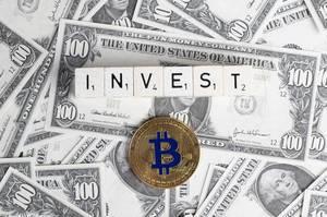 Bitcoin und das Wort INVEST (Investieren) mit Bitcoin-Münze auf Dollarnoten