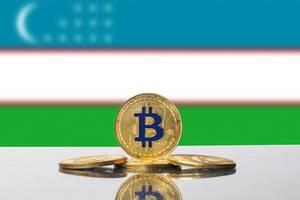 Bitcoins in Gold vor der Flagge des Landes Usbekistan