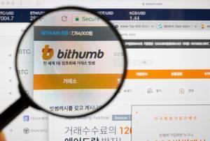 Bithumb-Logo am PC-Monitor, durch eine Lupe fotografiert
