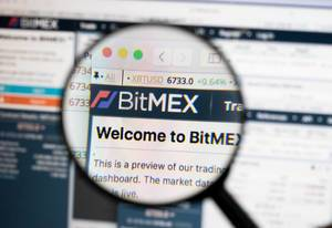 Bitmex logo on a computer screen with a magnifying glass