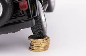 Black car on top of stack of coins on white background