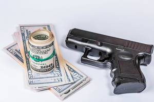 Black gun and dollars on white background