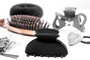 Black hair clips and hair bands with hairbrush on white background (Flip 2019)