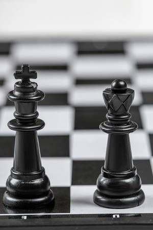 Black king and Queen chess pieces stand on a chessboard (Flip 2019)