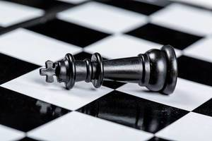 Black king chess piece lies on a chessboard. The concept of losing, losing and failing