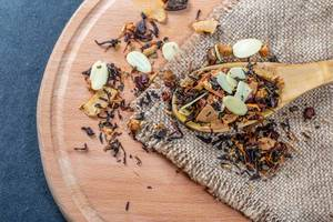Black tea with dried fruits and pieces of different nuts in a spoon on the burlap