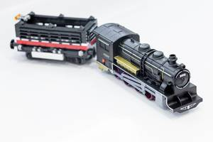 Black toy locomotive with a wagon on a white background (Flip 2019)