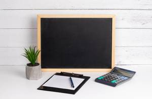 Blackboard with calculator and notepad