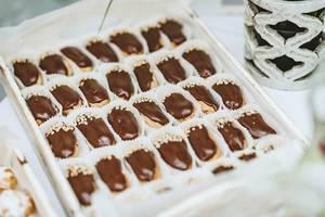Blätterteig-Gebäck mit Schokoladenguss, in Papierförmchen auf einem Holztablett angerichtet