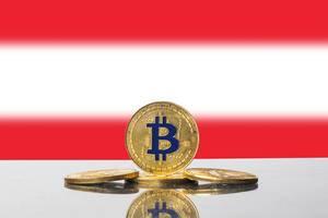 Blau-goldene Bitcoin-Münzen mit der rot-weißen Flagge Österreichs im Hintergrund