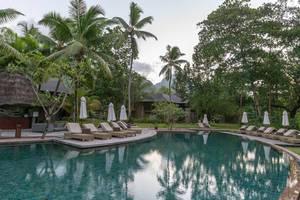 Blau-grüner Pool unter tropischen Palmen mit leeren Sonnenstühlen und Sonnenschirmen des Constance Ephelia Resort auf Mahé, Seychellen