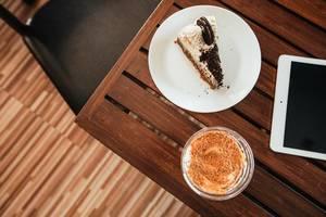 Blaubeer-Cheesecake mit Mango Eiscreme-Soda und einem iPad auf einem Holztisch - Aufsicht