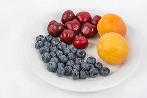 Blaubeeren, Aprikosen und mehrere Kirschen auf einem weißen Teller