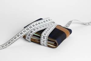 Blaubraune faltbare Geldbörse dicht umschlungen von einem weißen Maßband mit Aufruf zum Geldsparen - diagonale Nahaufnahme auf weißem Untergrund
