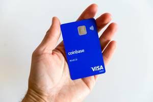 Blaue Coinbase-Karte mit Visa Debit Logo, mit Kryptowährungen wie mit Geld zahlen