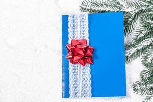 Blaue Grußkarte mit weißem Spitzenband und Roter Schleife