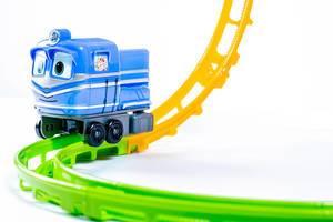 Blaue Spielzeugeisenbahn auf bunten Plastikschienen vor weißem Hintergrund