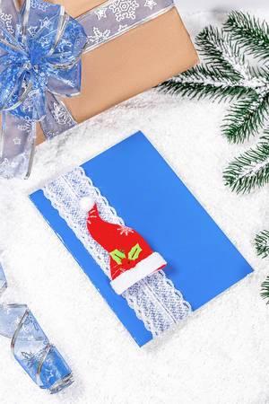 Blaue Weihnachtsgrußkarte mit roter Mütze und Tannenzweigen vor einem Geschenk im Schnee