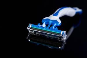 Blauer Einwegrasierer aus Kunststoff isoliert vor schwarzem Hintergrund mit Tiefenschärfe