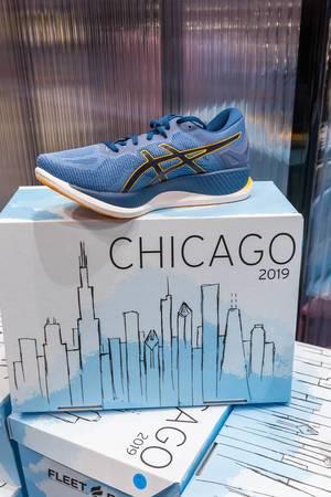 Blauer GlideRide Sportschuh von asics auf dem Schuhkarton im Chicago-Marathon 2019 Design