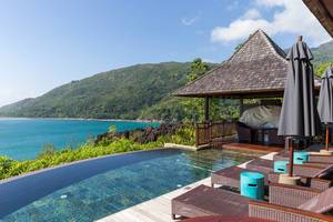 Blauer Infinity Pool und Sonnenliegen aus Rattan des Constance Ephelia Resort mit Blick auf den Indischen Ozean und Morne Nationalpark auf Mahé