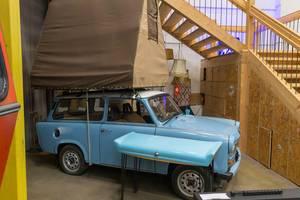 Blaues Retroauto mt weißem Dach und brauner Zeltkonstruktion auf dem Dach, als Wohnmobilalternative und Reisecaravan