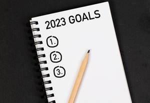 Bleistift und Notizheft mit Zielen für 2023 auf einem schwarzen Tisch