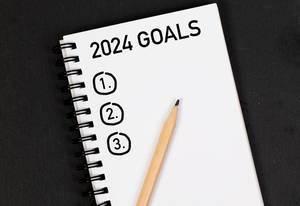 Bleistift und Notizheft mit Zielen für 2024 auf einem schwarzen Tisch