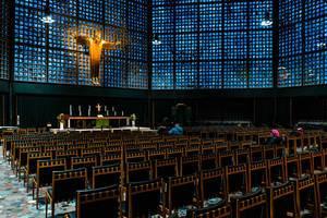 Blick auf den Innenraum der Kaiser-Wilhelm-Gedächtniskirche mit Jesusfigur an der blauen Fensterfront der Kaiser WIlhelm Gedächtniskirche in Berlin