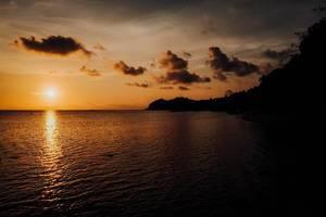 Blick auf den Sonnenuntergang in einem lokalen Badeort in Sipalay auf Negros, Philippinen, mit orangem Himmel und Reflexion auf dem Meer