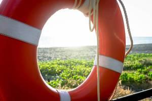 Blick auf den Strand durch einen orangefarbenen Rettungsring