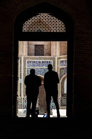 Blick auf die Schatten von zwei Männer in der Mir-i-arab Madrasa hinter den Türen der Kalon Moschee in Buchara, Usbekistan
