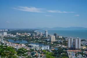 Blick auf die vietnamesische Küstenstadt Vung Tau mit Hochhäusern, dem Meer und Bergen am Horizont