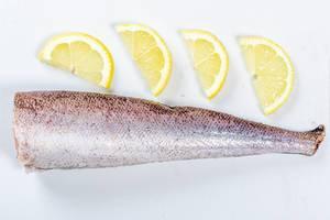 Blick auf ein rohes Stück Fisch, neben Zitronenscheiben