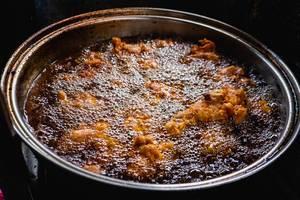 Blick auf Topf, in dem Hähnchenstücke in brodelndem Öl frittiert werden