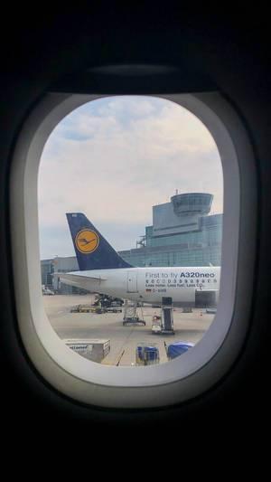 Blick aus einem Flugzeugfenster auf den Frankfurter Flughafen und den Airbus A320neo von Lufthansa, mit Gepäckband zum Frachtraum