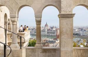 Blick durch die Säulen der Fischerbastei auf das Parlamentsgebäude und die Donau in Budapest