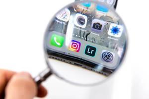 Blick durch Leselupe auf installierte Apps wie Instagram, Lightroom, Einstellungen, Kamera auf schwarzem Smartphone