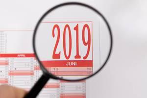 Blick durch Lupe auf Jahreskalender 2019 in rot-weiß